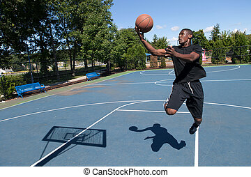 Basketball player driving to the hoop for a layup. Shallow depth of field. Contrasty shadow silhouette of backboard and player clearly visible.
