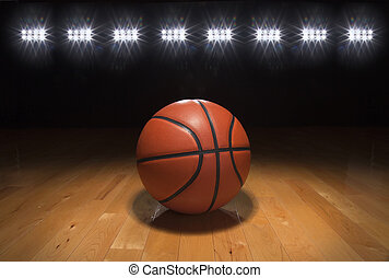 Basketball on wood floor beneath bright lights