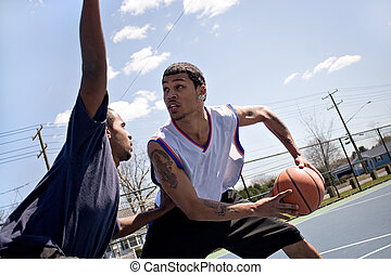 Basketball One On One - A young basketball player guarding...