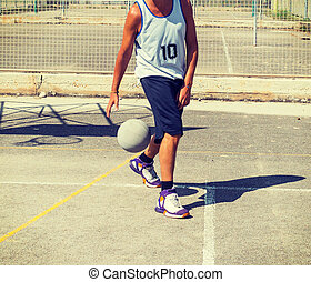 Basketball player dribbling betweeen the legs