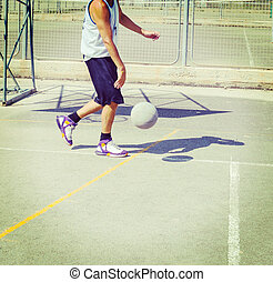 Basketball player dribbling in a playground