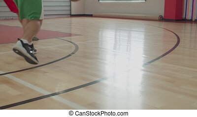Basketball player dribbling the ball in motion - Low section...