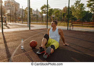 Basketball player drinks water on outdoor court