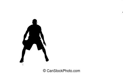 Basketball player fills the ball throws it forward. Silhouette. Slow motion