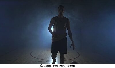 Basketball player goes straight to the camera in a dark room...