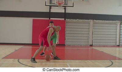 Skillful handsome african american defending basketball player in uniform guarding his opponent, playing man to man defense during one on one basketball game on indoor basketball court.