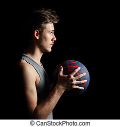 Basketball player holding ball on black