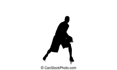 Basketball player in sports uniform stuffing the ball. Silhouette. Slow motion