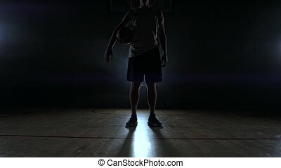 Basketball player in sportswear red shorts and a blue t-shirt goes on a dark basketball court in the backlighting coming out of the smoke knocks a basketball ball on the floor looking at the camera in slow motion