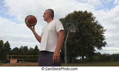Basketball player juggles basketball ball