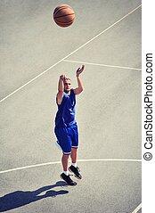 Basketball player jumping and shooting the ball