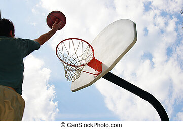 Basketball player jumping up toward the hoop