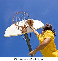 Basketball player jumps for basket