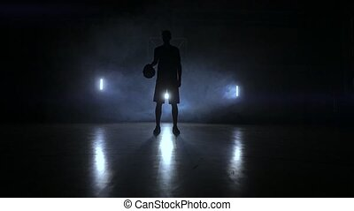 Basketball player knocks the ball in the light of the lamps...