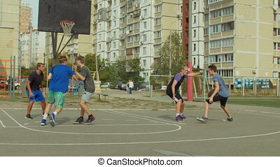 Teenage sporty basketball player dribbling and passing the ball to his teammate while playing streetball on court. Streetball player scoring points in the paint with layup shot during basketball game.