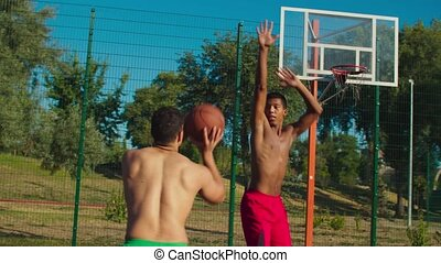 Rear view of active muscular build mixed race basketball player avoiding block from opposing defender, making fadeaway jump shot and scoring two points while playing streetball game on outdoor court.