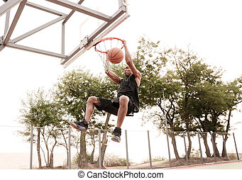 Basketball player practicing and jumping to hoop