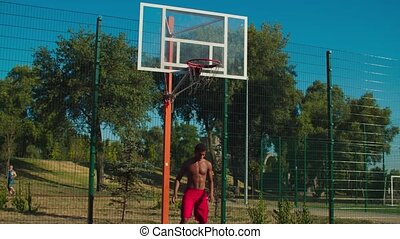 Shirtless fit african streetball player driving to the hoop, scoring two point field goals with layup shot after teammate assist while playing basketball game at urban court in neighborhood in morning