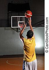 Basketball player shooting ball to basket