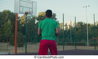 Rear view of athletic african american basketball player in sportswear, shooting and scoring two point field goals after assist of teammate during playing streetball game on outdoor court at sunrise.