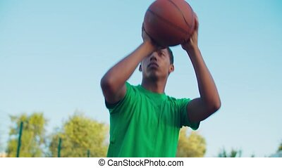Portrait of concentrated athletic african american streetball player making attempt to score field goals during playing basketball on outdoor court in early morning, looking determined and confident.