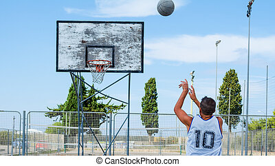 Basketball player shooting in a playground