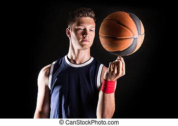 Basketball player spinning ball on finger - studio shoot