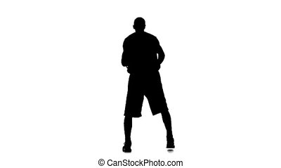 Basketball player spinning passes the ball behind his back. Silhouette