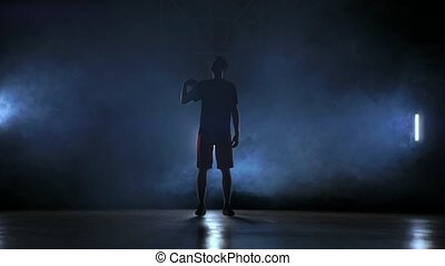 Basketball player throws and catches the ball in the smoke.