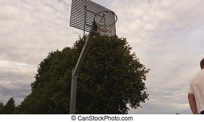 Basketball player trains shot at the basket