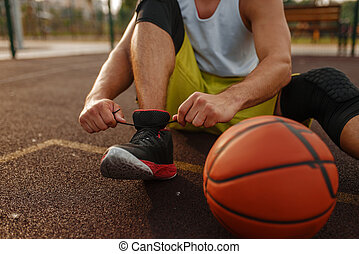 Basketball player tying laces on outdoor court