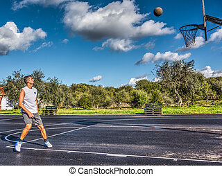 Basketball player waiting for the ball to get inside the hoop