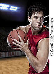 Basketball player with a ball in his hands and a red uniform...