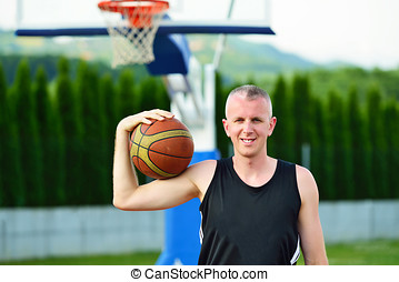 Basketball player with ball at the outdoors basket court