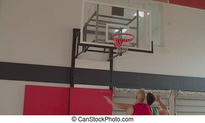 Opposing basketball players boxing out to maintain better rebounding position than opponent by widening stance and arms, using body as barrier while playing basketball game on indoor court.