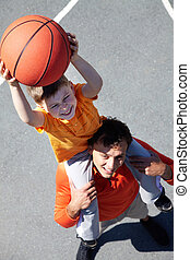 Basketball players - Image of young man and his son playing...