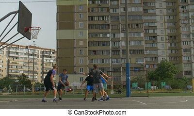 Basketball players in action playing outdoors - Sporty...