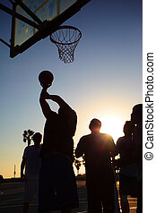 Basketball players silhouettes at sunset