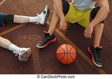 Basketball players sitting on the ground outdoor