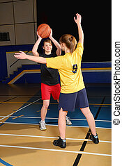Two girls play basketball in a high school gym.