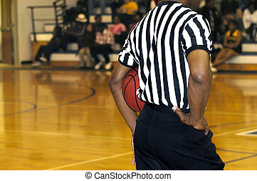 Basketball Referee stands mid court holding basketball under his arm