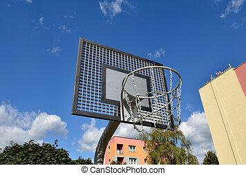 Basketball rim, streetball hoop against blue sky.