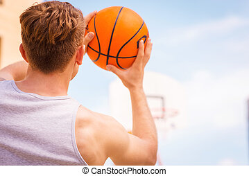 Basketball shooting action. Rear view of young male basketball player ready for the shot