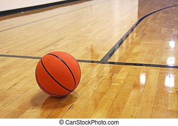 Single basketball on hardwood court