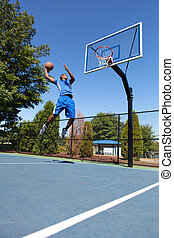Basketball Slam Dunker - Young basketball player drives to...