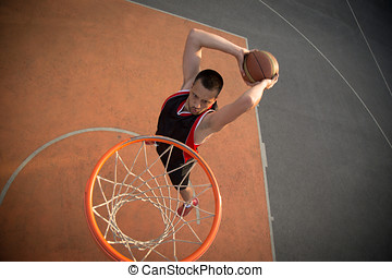 Basketball street player making a slam dunk