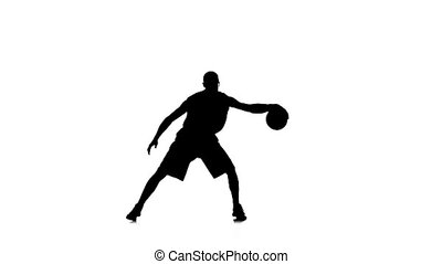 Basketball is in one place and stuffing the ball under his foot back and forth. White background. Slow motion. Silhouette