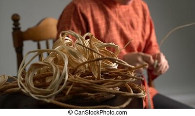 View of craftsman weaves basket in studio - Basketry. View...