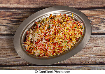 Basmati rice with spices and vegetables isolated on wooden background. Top view. Indian food