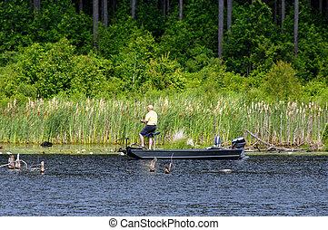 Bass Fishing on Lake - Fisherman trolls a new lake in...